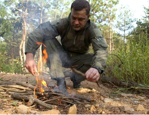 Maj. Paul Neidhardt starts a fire using a block of flint during combat search and rescue training Sept. 21 near Osan Air Base, South Korea. Annual training is conducted by survival, evasion, resistance and escape instructors to reacquaint aircrew members with combat search and rescue procedures and techniques. Major Neidhardt is with the 25th Fighter Squadron at Osan AB. (U.S. Air Force photo/Airman 1st Class Chad Strohmeyer)