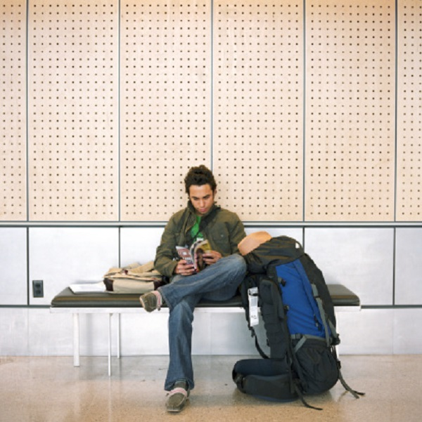 Young man sitting on bench with backpack, reading magazine
